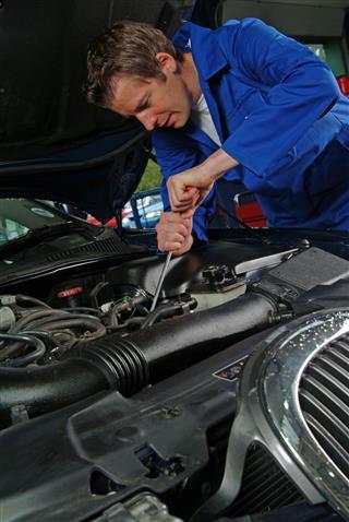 Mechanic Working On A Jaguar Engine