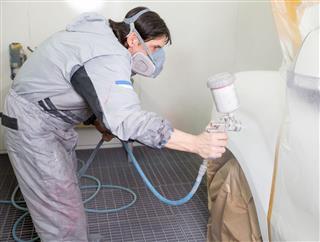 Painter Spraying Paint On Bodywork Parts