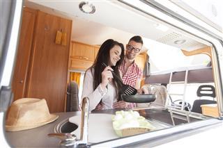Couple Making Breakfast In Camper Van
