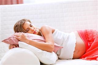 Pretty pregnant woman sleeping on sofa