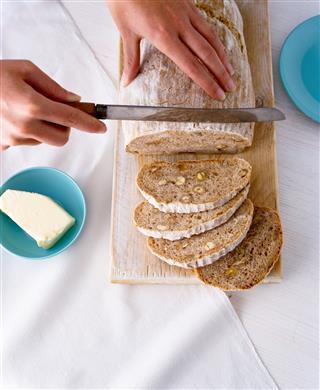 Woman Slicing Hazelnut Bread