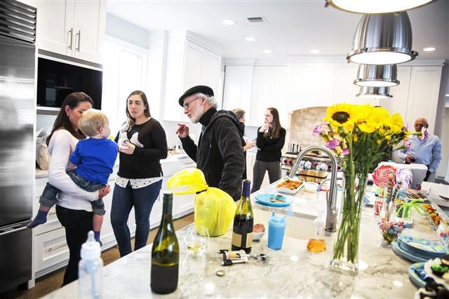 Family in kitchen celebrating boy's first birthday