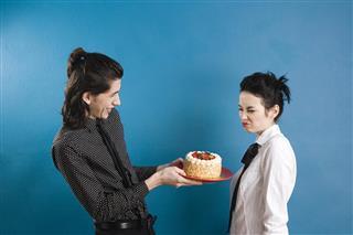 Man offering cake to grimacing woman