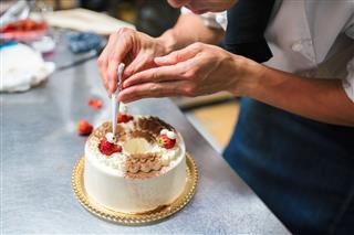 Baker Decorating A Cake