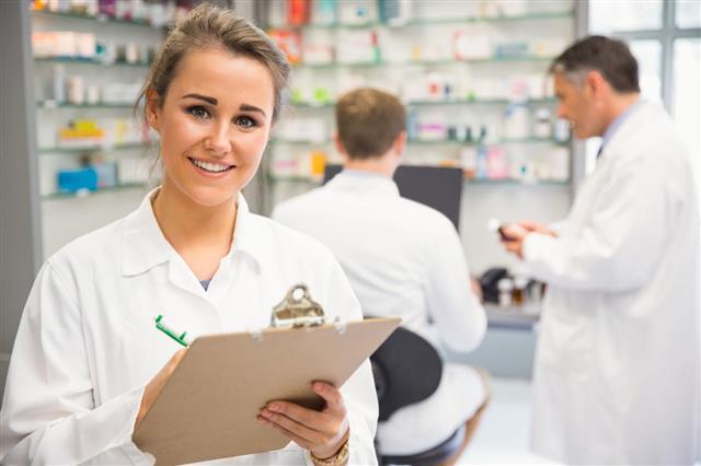Junior Pharmacist Writing On Clipboard