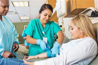 Nurse Bandaging Arm Of Patient