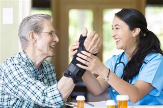 Nurse Examines Senior Mans Wrist