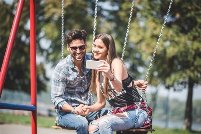 Couple On Swings Taking A Selfie