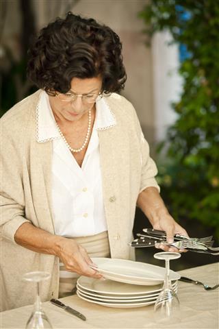 Senior Woman Setting Table