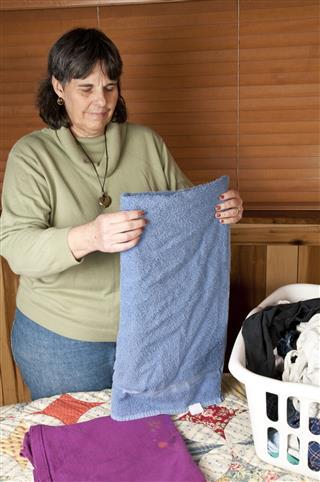 Mature Woman Folding Laundry