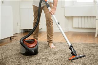 Man Vacuum Cleaning Carpet