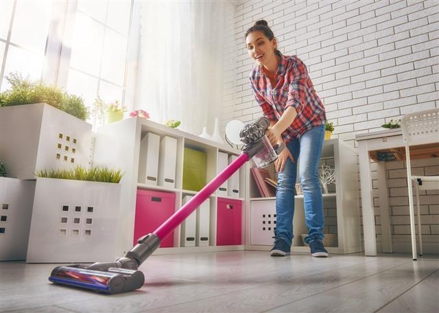 Woman Vacuums The Floor