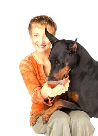 Woman Feeding Hungry Pet Dog