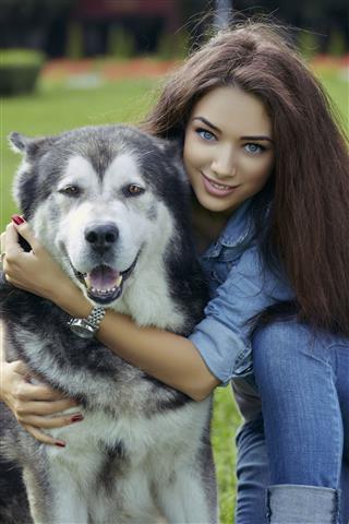 Beautiful Woman With Malamute Dog