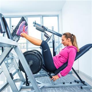 Woman Exercising On Leg Press Machine