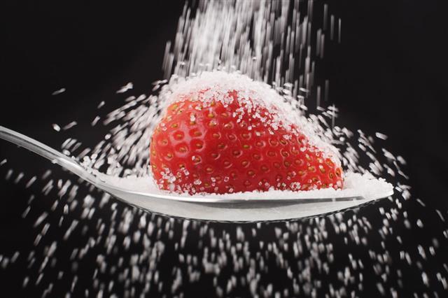 Pouring Sugar Onto Strawberry