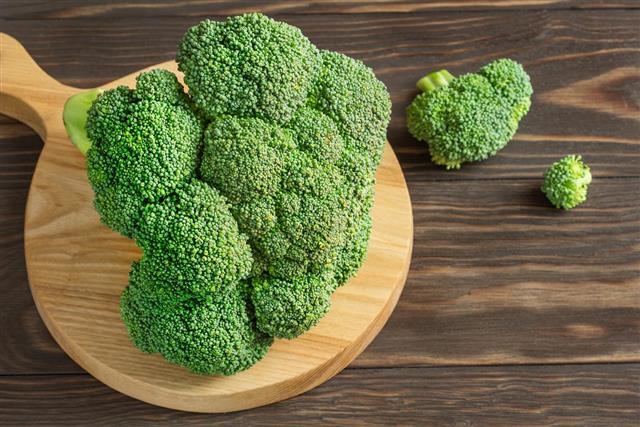 Fresh raw green broccoli on a wooden board