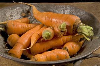 Raw carrots in vintage colander