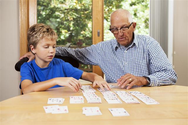 Grandfather Teaching Grandson Playing Card