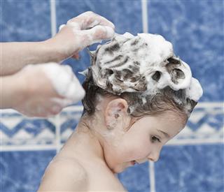 Cute Little Girl Washing Hair In Bath