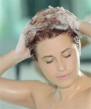 Woman Applying Shampoo On Hair