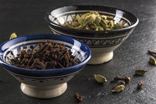 Cardamom And Cloves In Ceramic Bowls