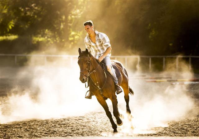 Man Horseback Riding At Sunset