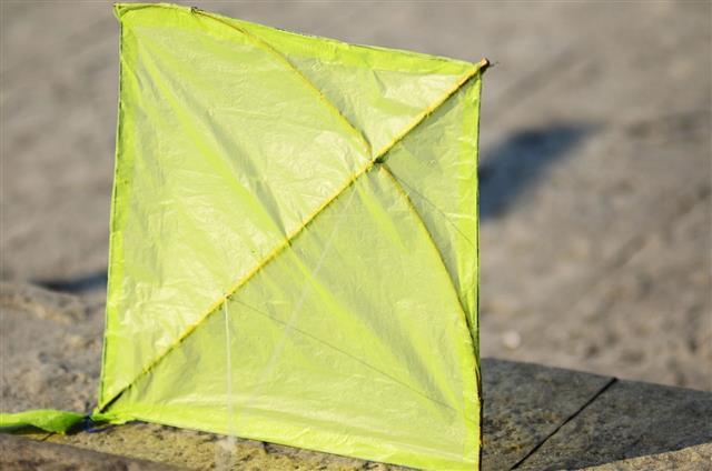 Green Kite On Concrete Floor