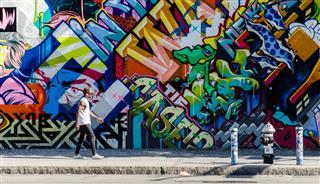 Male Walking Next To Wall Of Graffiti