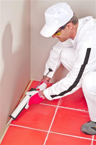 Worker Lays Silicone Sealant Corner Floor