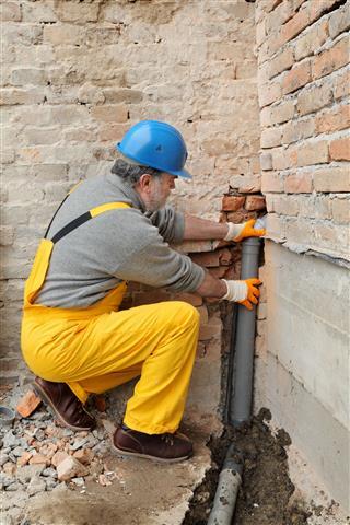 Plumber Installing Sewerage Tube