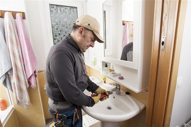 Plumber Fixing Bathroom Faucet