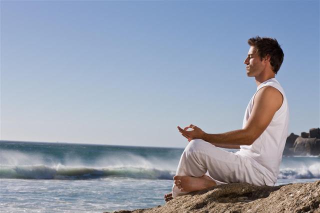 Man Meditating On Rock By Sea