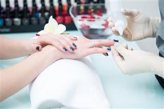 Beautician Varnishing Nails at Beauty Salon, Europe