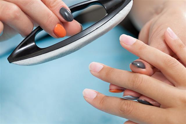 Studio nail. Beautician polishing female nails
