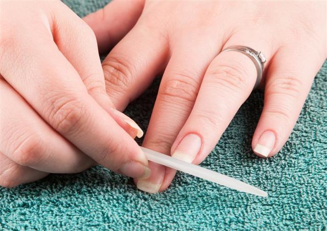 Woman making manicure herself