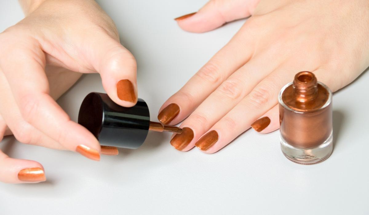 Woman Lying Bronze Polish To Nails