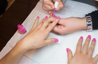Nail technician painting customers nails pink