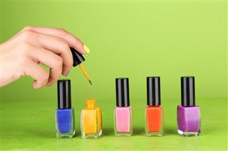 Female hand with stylish nails holding bottle with nail polish
