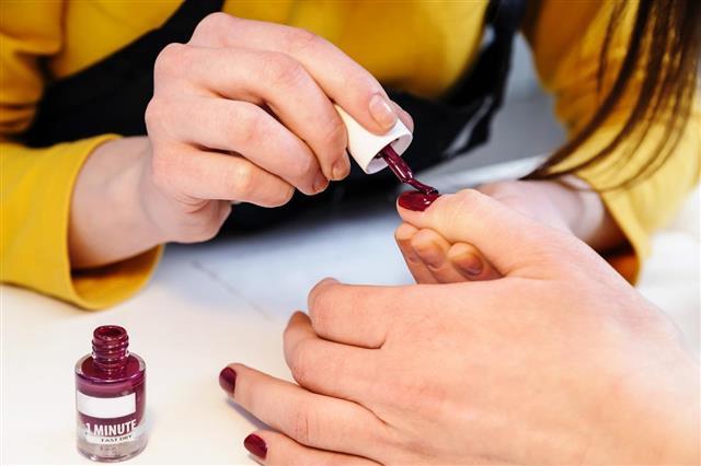 Manicurist is applying nail varnish