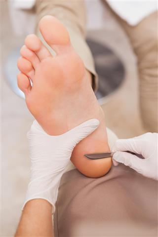 Pedicurist removing dead skin