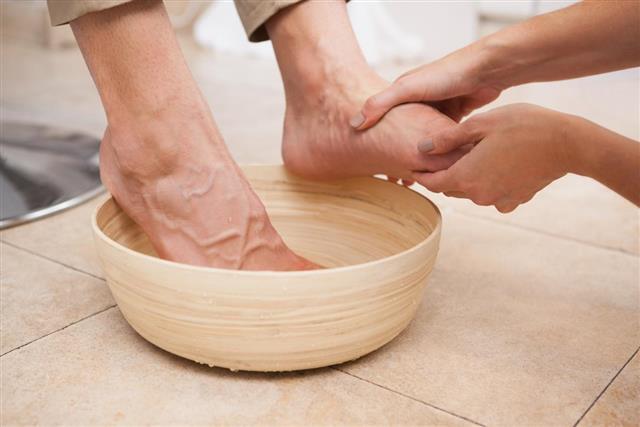 Pedicurist cleansing customer feet