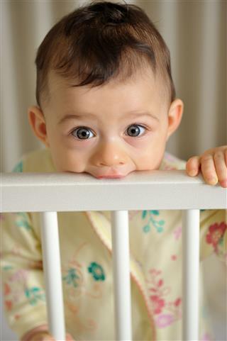 Baby Teething On White Crib