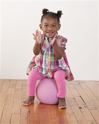Toddler Girl Sitting On Ball