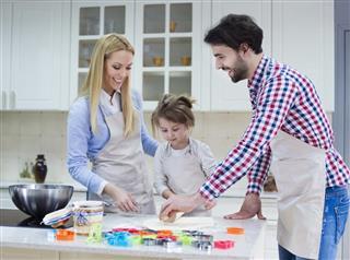 Smiling family baking Christmas cakes