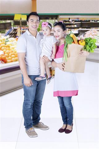 Family shopping vegetables in supermarket