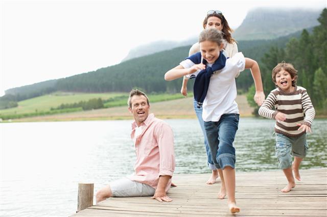 Children Running On Pier By Lake