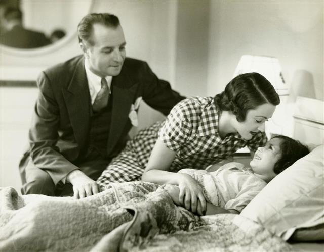 Parents tucking daughter