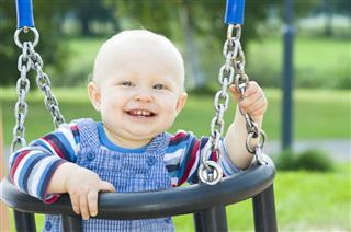 Little Boy Sitting On A Swing