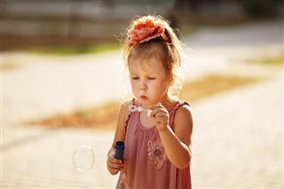 Little Girl Blowing Soap Bubbles In Park